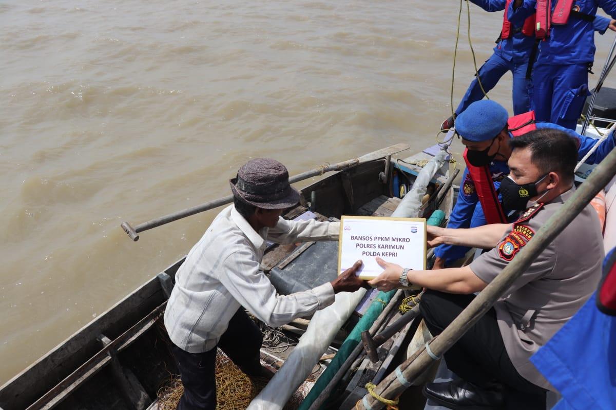 Ket foto: Kapolres Karimun, AKBP Muhammad Adenan saat memberikan bantuan sosial kepada salah seorang nelayan tradisional di tengah laut