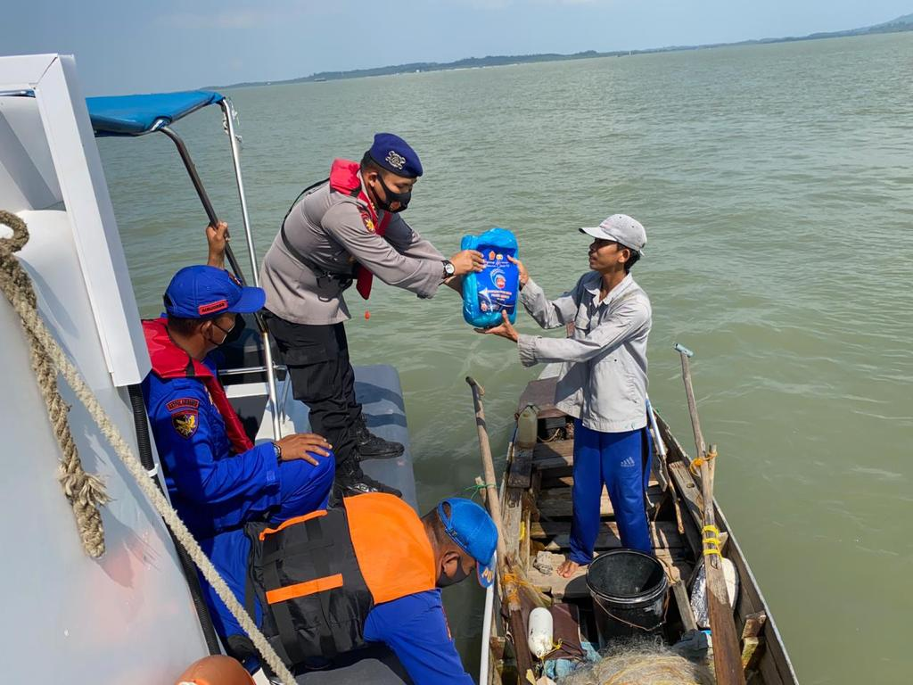 Ket foto: Kasatpolairud Polres Karimun, Iptu S Binsar Samosir, SH,MH saat membagikan bantuan sembako program PPKM Mikro kepada salah seorang nelayan