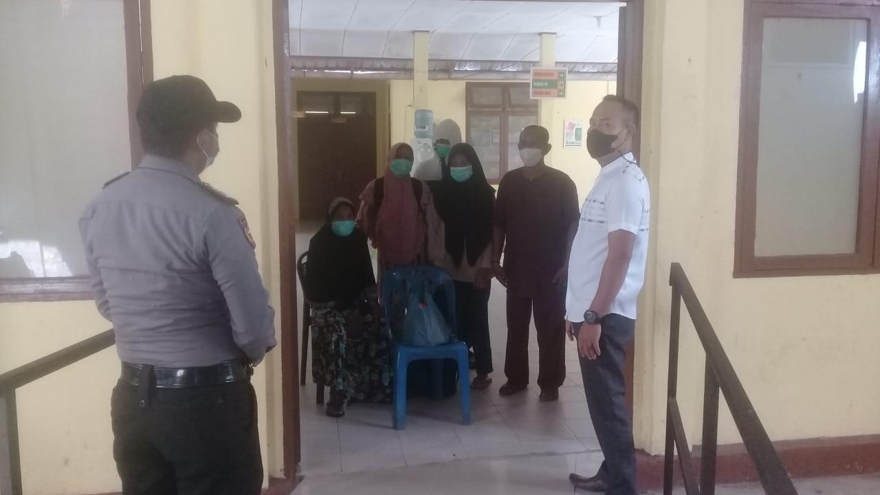 Foto Personil Polsek Tebingtinggi Barat saat menyalurkan extra puding kepada pasien yang sedang menjalani isolasi di UPT Puskesmas Alai.