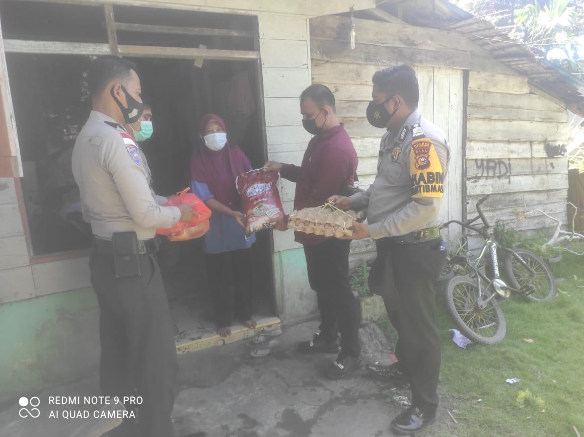 Foto Personil Polsek Rangsang Barat saat melakukan pembagian sembako kepada warga.